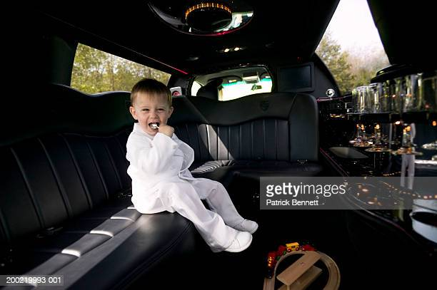Boy (2-4) sitting in limousine, holding spoon in mouth