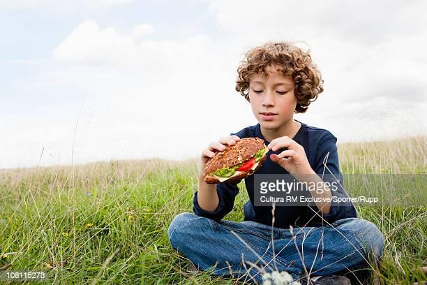 Boy sitting in meadow eating sandwich