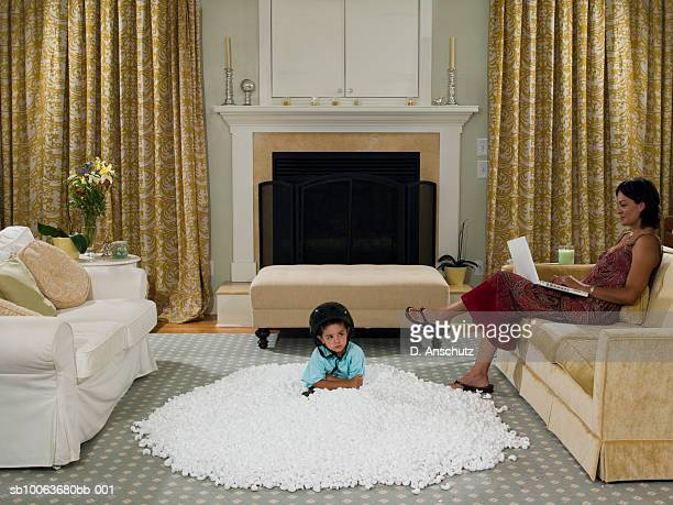 Boy (3-4) sitting in pile of packing peanuts, mother reading on sofa
