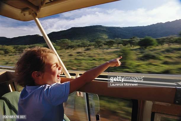 Boy (5-7) sitting in safari vehicle, pointing (blurred motion)