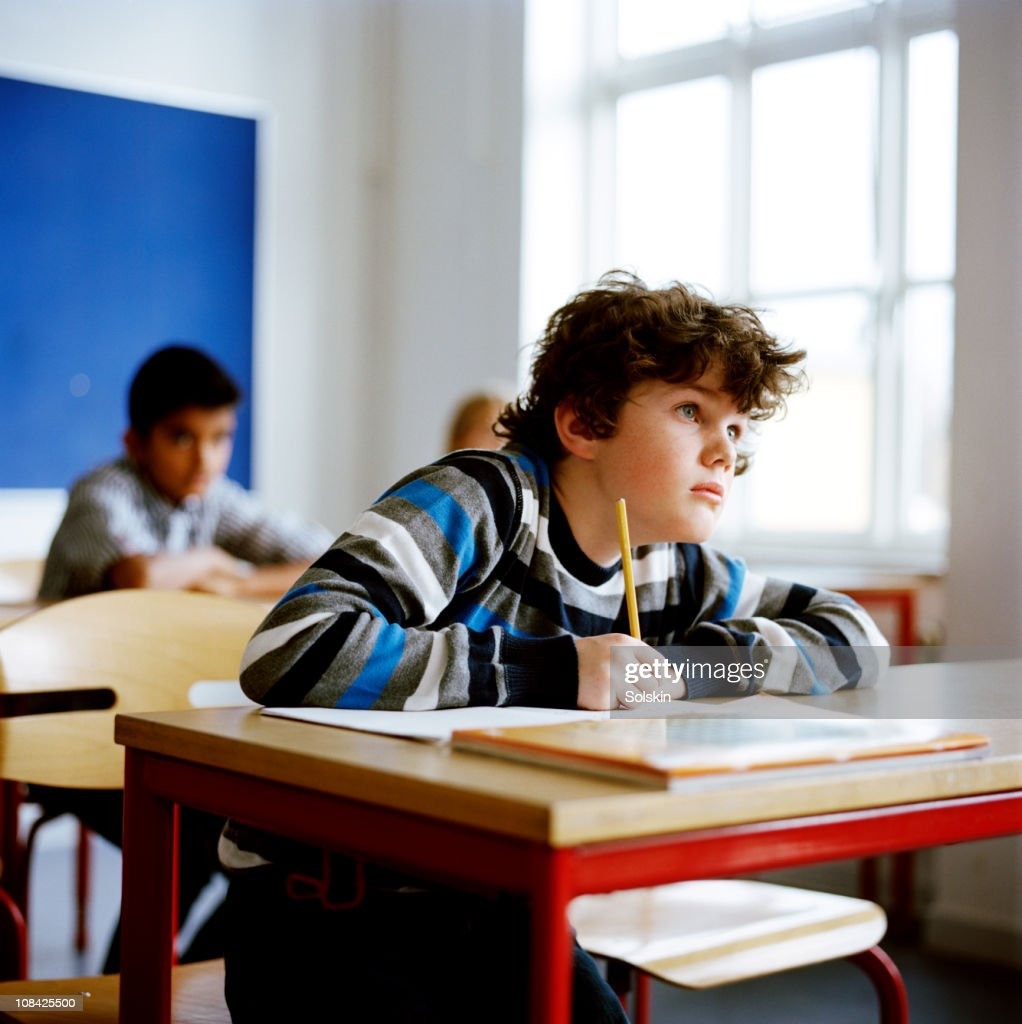 Boy sitting in school class : Stock Photo