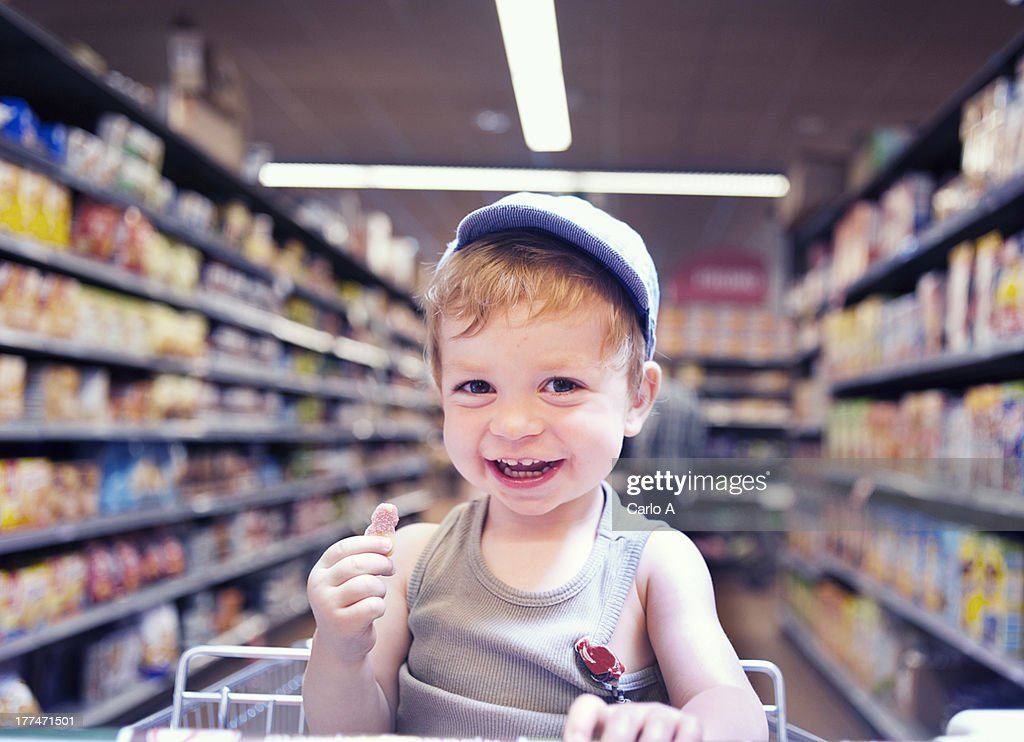 Boy sitting in shopping trolley : Stock Photo