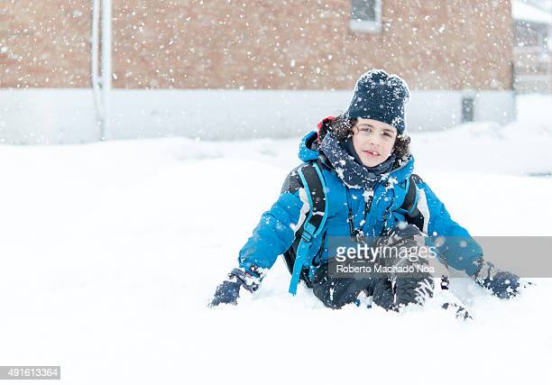 Boy sitting in snow and enjoying the Canadian Winter He is wearing a thick blue jacket black pants black gloves and a black hat There is a brown...