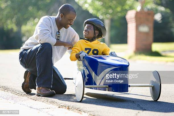 Boy Sitting in Soapbox Car Talking to Father