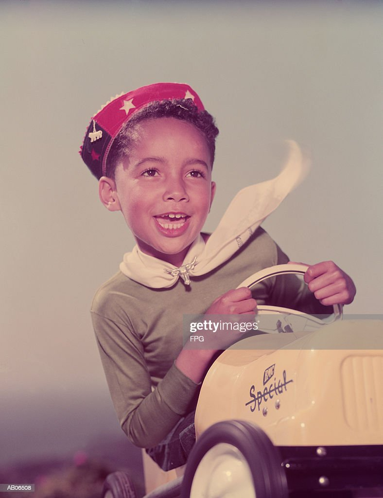 Boy (5-7) sitting in toy car : Stock Photo