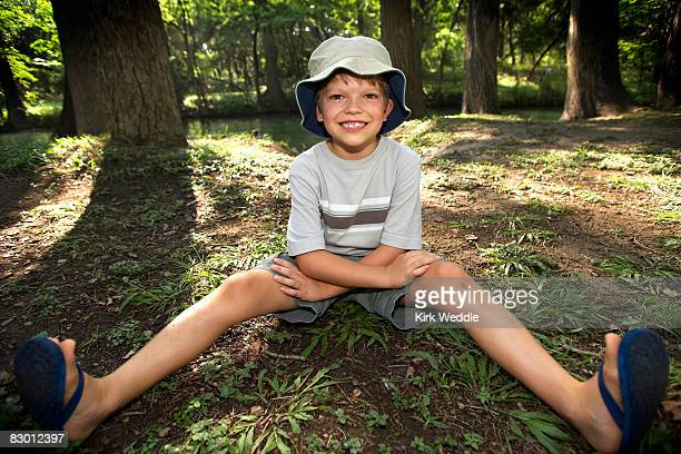 Boy (8), Sitting in Woods, Feet Out