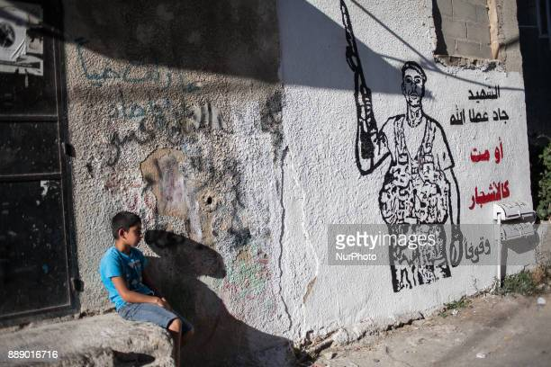 Boy sitting next to graffiti of Palestinian militant In 2014 Israel launched military operation on 8 July 2014 in the Hamasruled Gaza Strip Following...