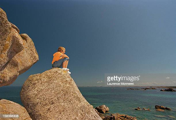 Boy sitting on a big rock facing the ocean