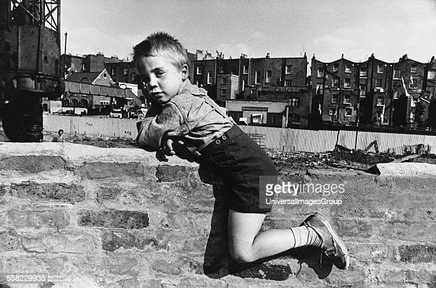 Boy sitting on a brick wall Portobello Road London UK 1964