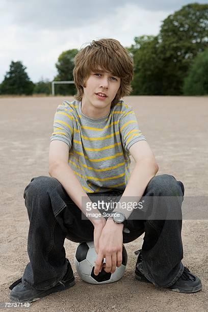 Boy sitting on a football