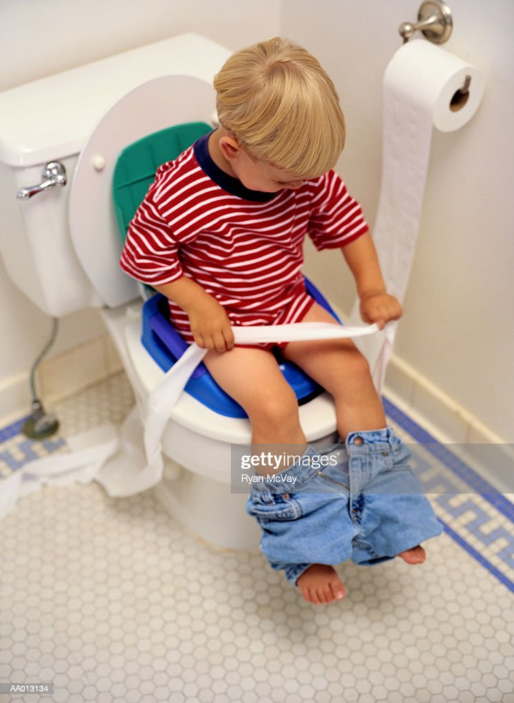 Boy Sitting On A Potty Chair With Toilet Paper Stock Photo