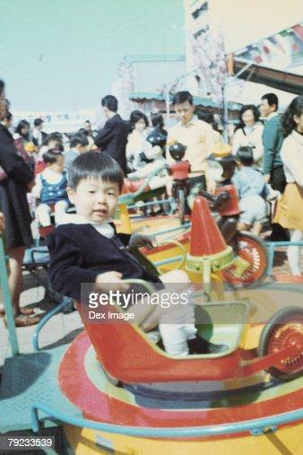 Boy sitting on a spaceship ride : Stock Photo