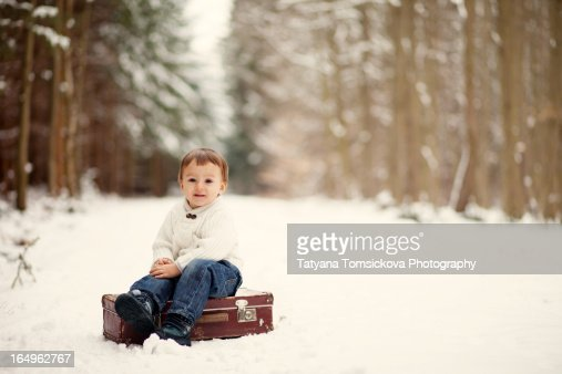 Boy, sitting on a suitcase in the forest : Stock Photo