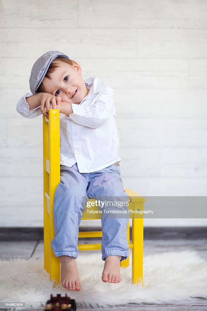 Boy, sitting on a yellow chair, smiling : Stock Photo