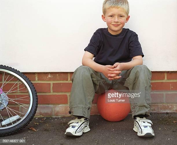 Boy (7-9) sitting on basketball by wall, portrait