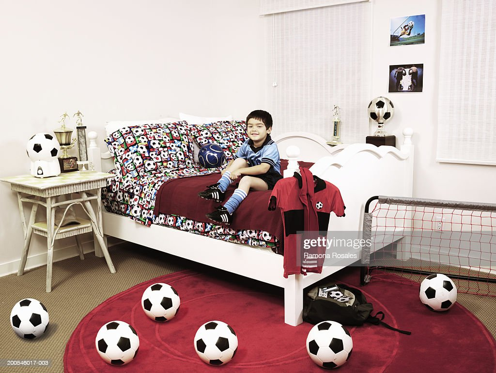 Boy (4 6) Sitting On Bed In Soccer Themed Bedroom : Stock Photo