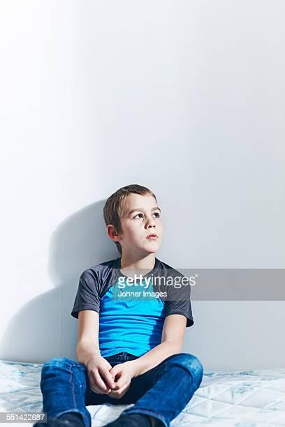 Boy sitting on bed