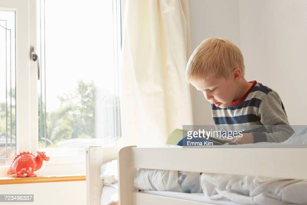 Boy sitting on bed reading a book