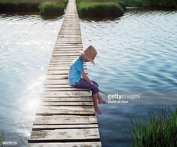 Boy sitting on bridge