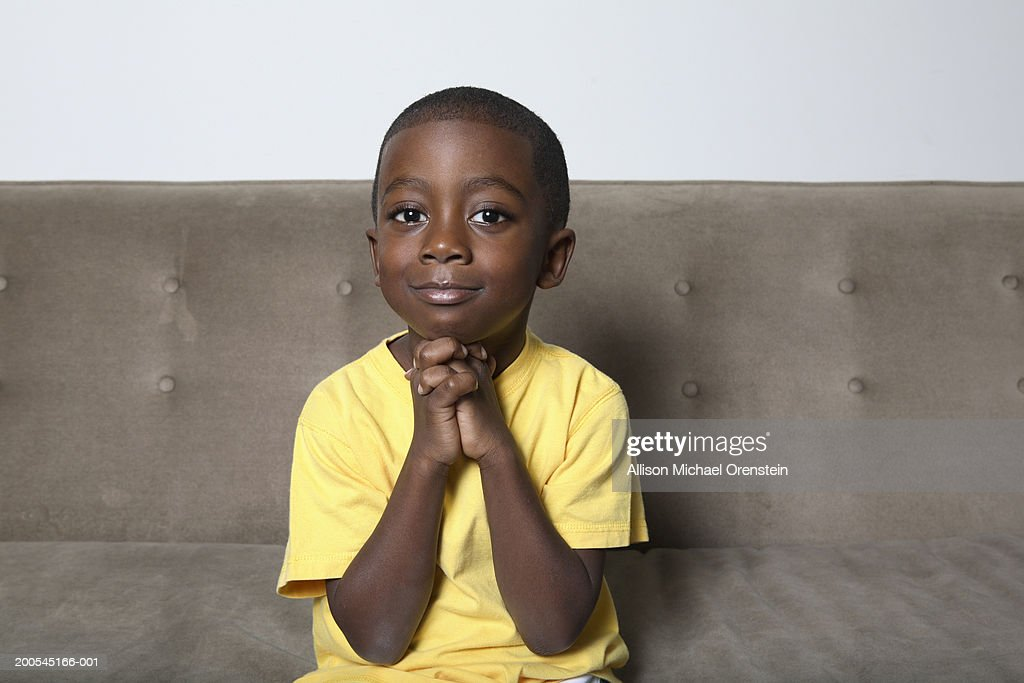 Boy (4-5) sitting on couch with hands clasped : Stock Photo