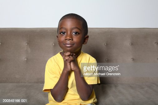 Boy (4-5) sitting on couch with hands clasped : Foto de stock
