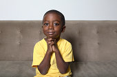 Boy (4-5) sitting on couch with hands clasped