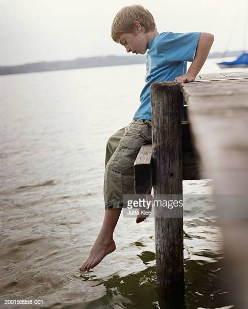 Boy (8-10) sitting on edge of jetty, dippng toes in water