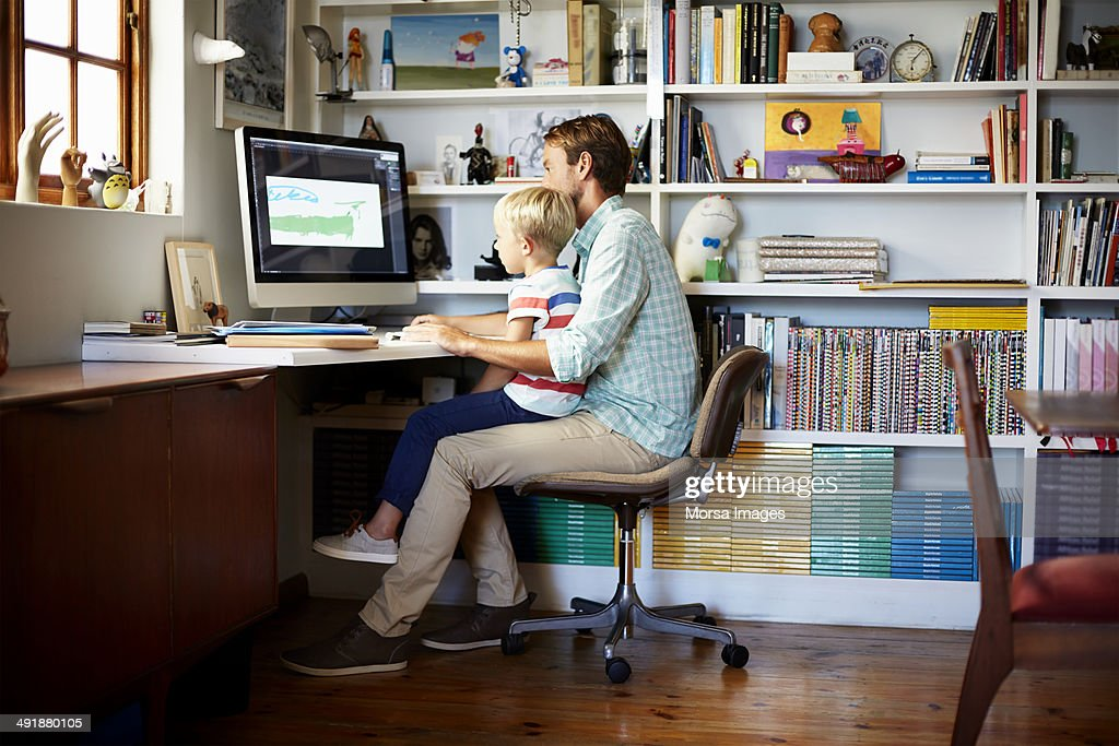 Boy sitting on father's lap at computer desk