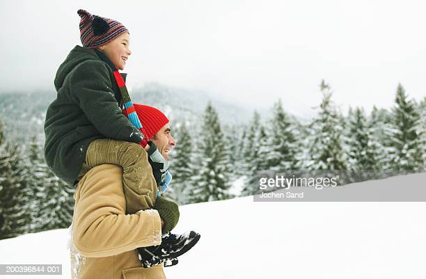 Boy (8-10) sitting on father's shoulders in snow, profile, close-up