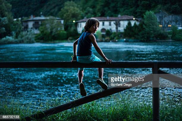 Boy sitting on fence by river looking over shoulder at camera