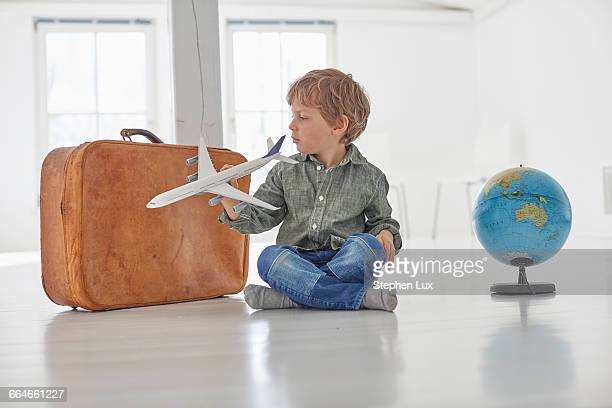 Boy sitting on floor playing with toy airplane