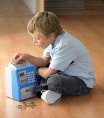 Boy (7-9) sitting on floor putting coins in money box