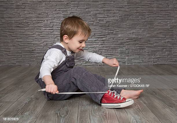 Boy sitting on floor putting on shoes