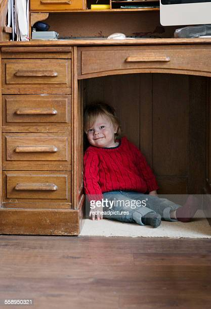 Boy sitting on floor under desk