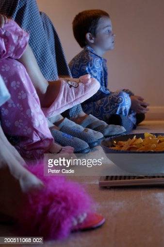 Boy (3-7) sitting on floor watching television with family, side view : Stock Photo