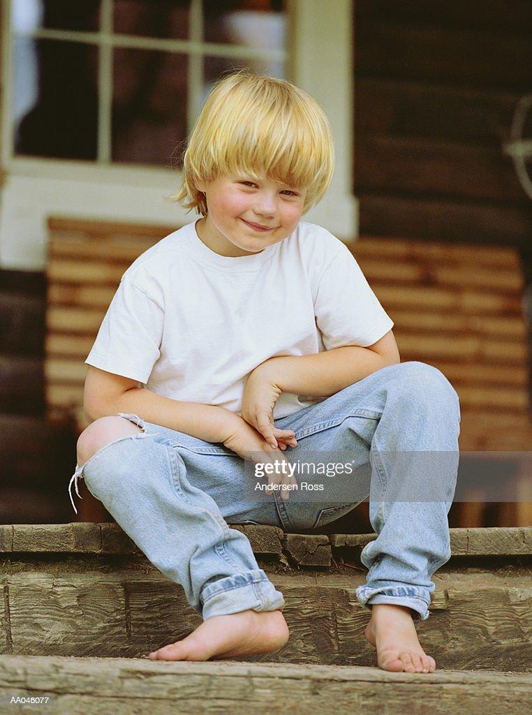 Boy (5-7) sitting on front porch, portrait : Stock Photo