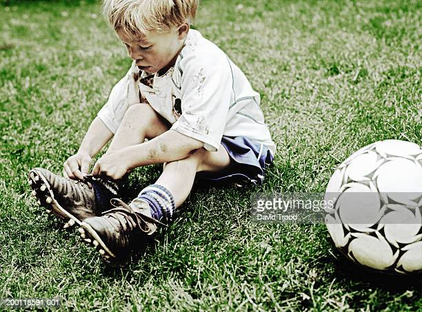 Boy (6-8) sitting on grass tying laces of football boots