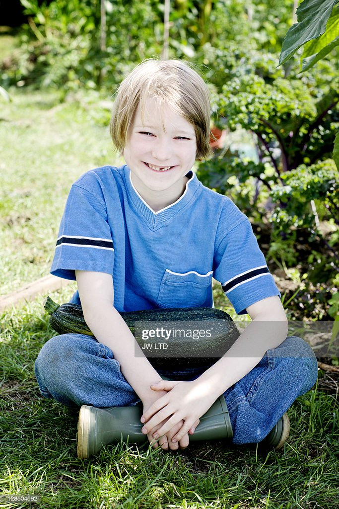 Boy sitting on grass with marrow, portrait : Stock Photo