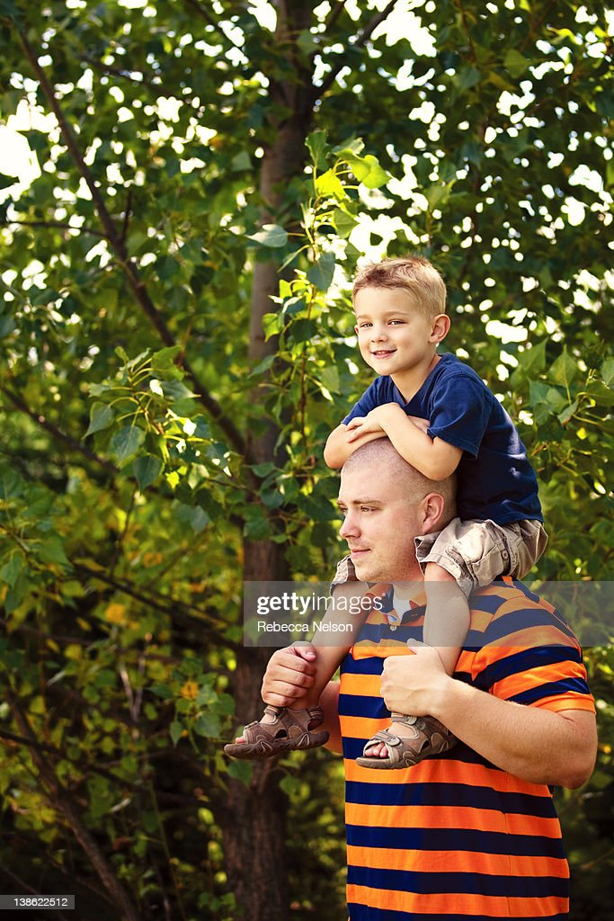 Boy sitting on his father's shoulders : Stock Photo