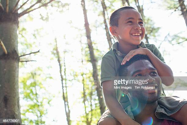 A boy sitting on his father's shoulders.