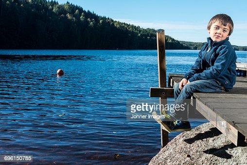 Boy sitting on jetty
