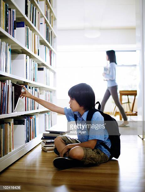 boy sitting on library floor, choosing book