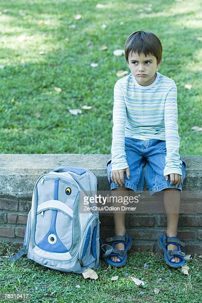 Boy sitting on low wall, backpack by side, looking away