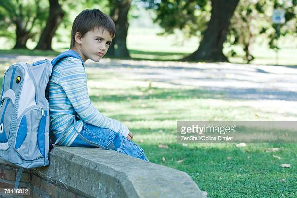 Boy sitting on low wall, wearing backpack