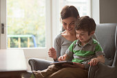 Boy sitting on mothers lap and using digital tablet