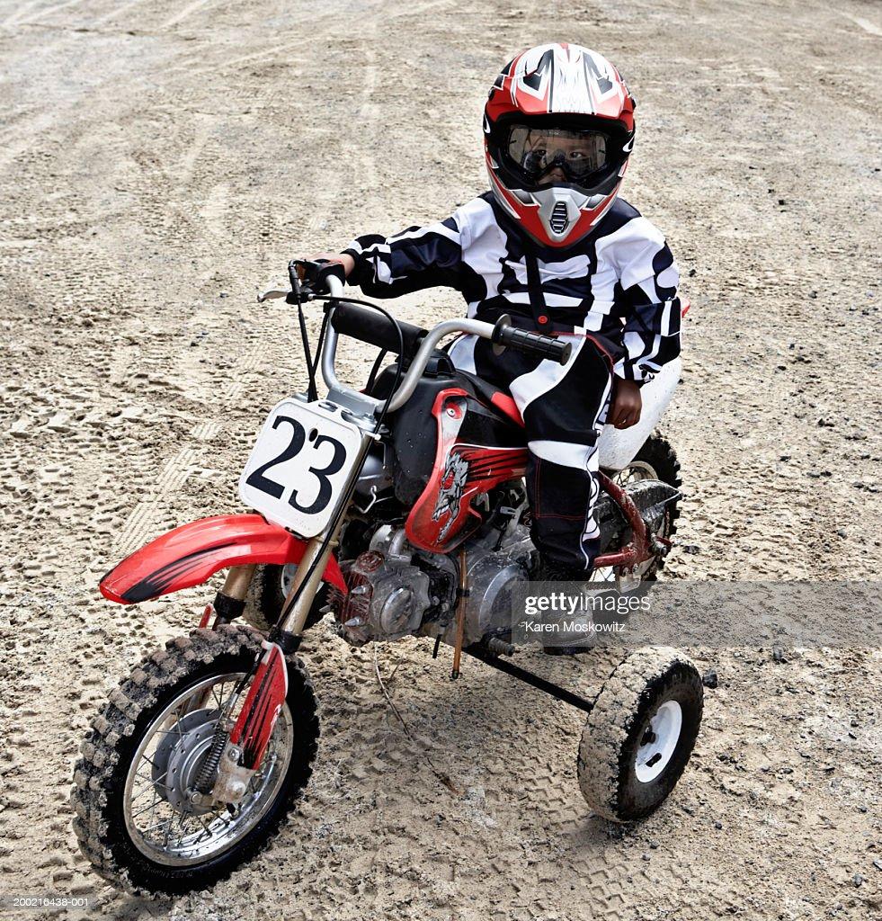 Boy (2-4) sitting on motocross bike, wearing protective gear, portrait : Stock Photo