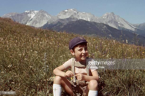 Boy sitting on mountain meadow
