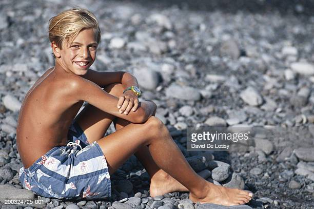 Boy (10-11) sitting on pebble beach, looking over shoulder, smiling