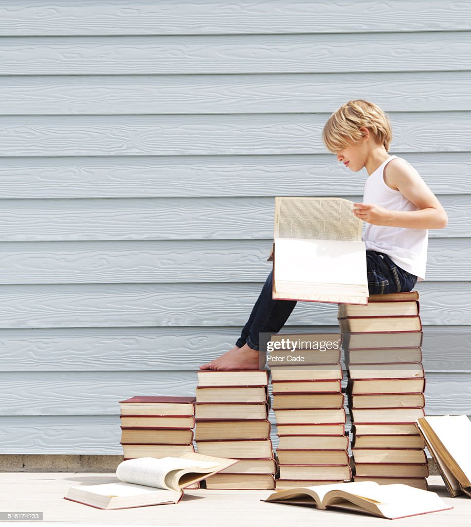 boy sitting on pile of books . Boy reading book.
