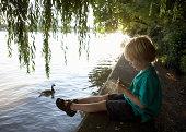 Boy (3-5) sitting on riverbank feeding ducks